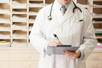 Medical doctor writing the paper in front of the cabinet of patient cards.