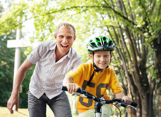 Father learn his son to ride bicycle