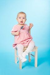 little girl with spoon sitting on chair