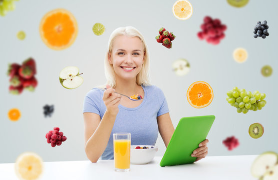 smiling woman with tablet pc eating breakfast