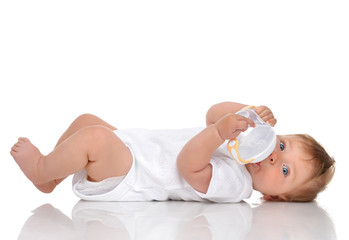 Infant child baby kid lying and drinking water from the feeding