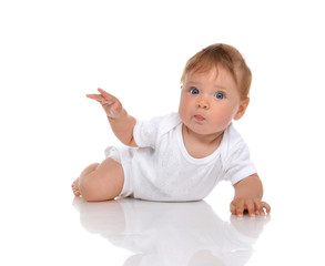 Infant child baby girl lying surprised with hand pointing
