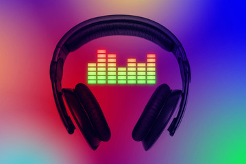 Headphones over colorful background with color equalizer