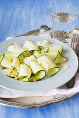 Raw Vegetarian Carpaccio Made with Zucchini Slices, Roasted Pine Nuts and Parmesan Shavings
