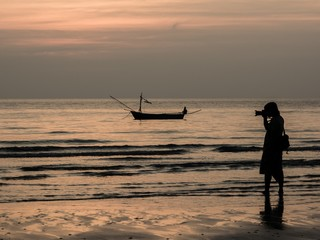 A photographer capturing a boat in the sunset