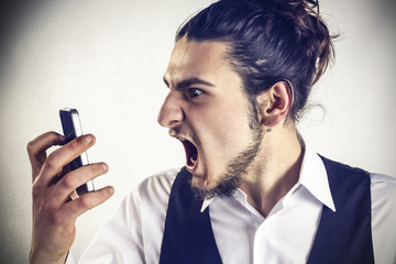 Angry young man screams at the cellular phone