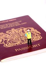 Miniature security officer passport. Miniature scale model security officer standing on passport.