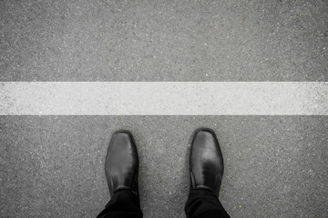 Shoes standing in front of white line