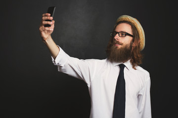 Hipster businessman with glasses and hat taking self portraits with his smartphone