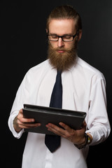 Portrait of serious hipster bearded businessman with documents. Boss in glasses posing in  business suit on black background.