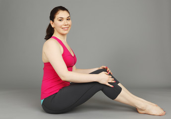 A seated young woman in exercise clothing smiling at viewer.