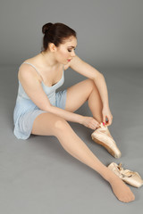 A seated ballerina tying up her ballet slipper.