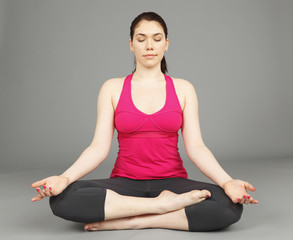 A young woman with eyes closed in the lotus position.