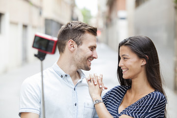 cheerful young couple making a selfie with a smartphone and selfie stick