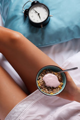 Woman eating healthy breakfast in the bed