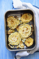 Oven baked cabbage slices in baking form at rustic blue painted background