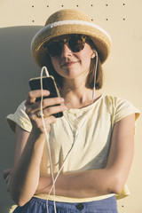 Beautiful young hipster Caucasian woman with smartphone and earp