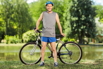 Cheerful senior cyclist posing in front of his bicycle by a pond