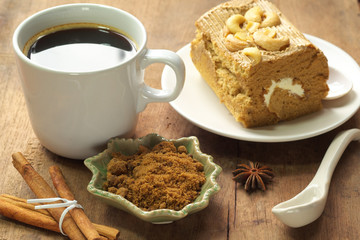 Hot black coffee with cakes and spices
