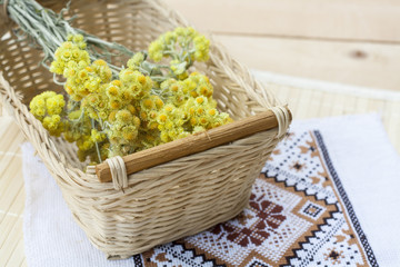Dwarf everlast flowers bouquet in a wicker basket and napkin with embroidery on light wooden table, selective focus