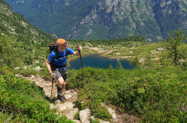 Fotomurales - Hiker on a trail near a lake in the mountains of Ticino, Switzerland.