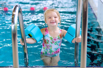 Little child enjoying swimming pool. Cute toddler girl wearing colorful swimsuit and armbands having fun in the water. Adorable sportsman kid promoting healthy lifestyle.