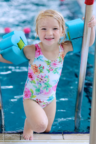 54cc18947d54 Little child enjoying swimming pool. Cute toddler girl wearing colorful  swimsuit and armbands having fun in the water. Adorable sportsman kid  promoting ...