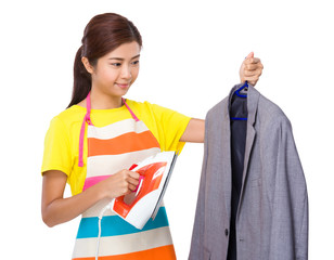 Young housewife using the steam iron for suit jacket