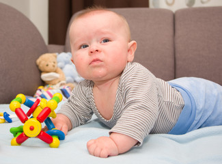 Angry infant boy playing with bright toys on a blue blanket