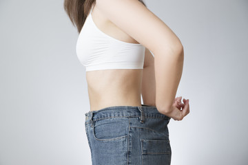 Young woman in jeans of large size, concept of weight loss