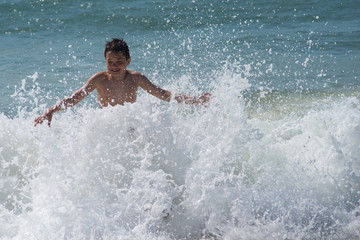 Boy playing with waves in sea