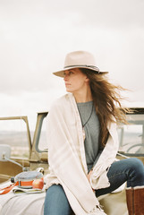 Woman wearing a hat sitting on the front of a jeep looking around her.