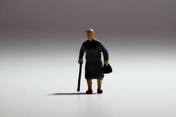 Miniature senior lady walking stick. Backlit miniature senior lady with walking stick.