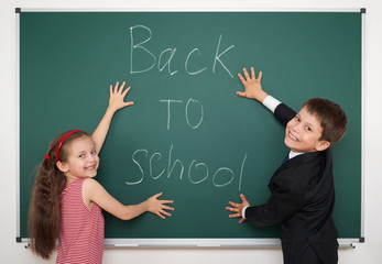 boy and girl write back to school on board