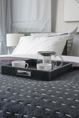 black tray of coffee cup on black blanket in modern bedroom