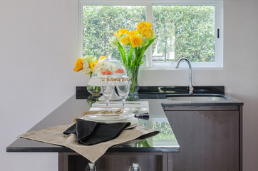 black counter in pantry with vase of plant and modern sink