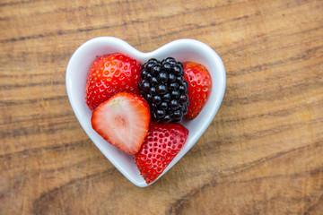 Erdbeeren und Brombeeren in herzförmige Schale