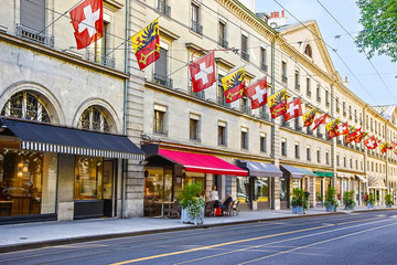 Geneva city street Rue Carraterie  view in summer with swiss flags on the street