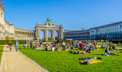Fotorolgordijn Brussel People are relaxing next to cinquantenaire monument in brussels during first sunny weekend in March.
