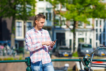 Young caucasian man writing message by phone outdoor in european