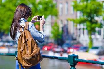 Young woman tourist taking photo on beautiful view of european