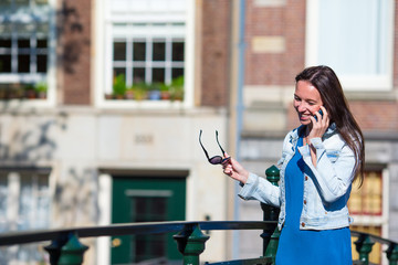 Young happy girl talking by cell phone in european city