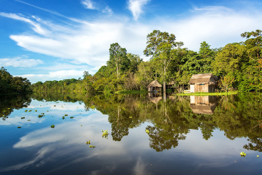 Small wooden shack in the Amazon rain forest with a beautiful reflection on the Yanayacu River near Iquitos, Peru