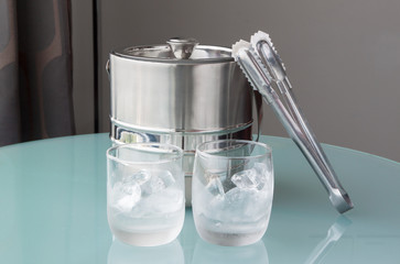 Glass of cold water and ice with stainless bucket