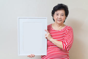 Asian woman holding empty white picture frame in studio shot, sp