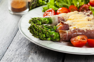 Baked green asparagus with prosciutto and cheese