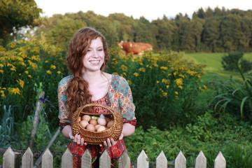 Junge Frau mit einem Korb mit frischen Hühnereiern