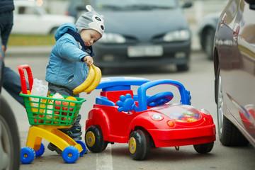 little boy on supermarket parking