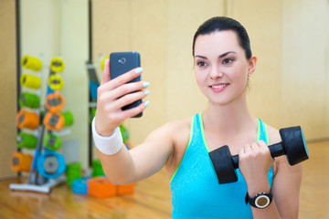beautiful sporty woman making selfie photo with dumbbell on smar
