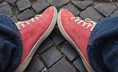 Wall Mural - Feet in red sneakers and jeans outdoors.